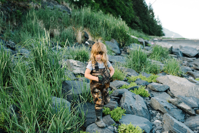 Girl wearing camouflaged waders walking over a rocky area near a river