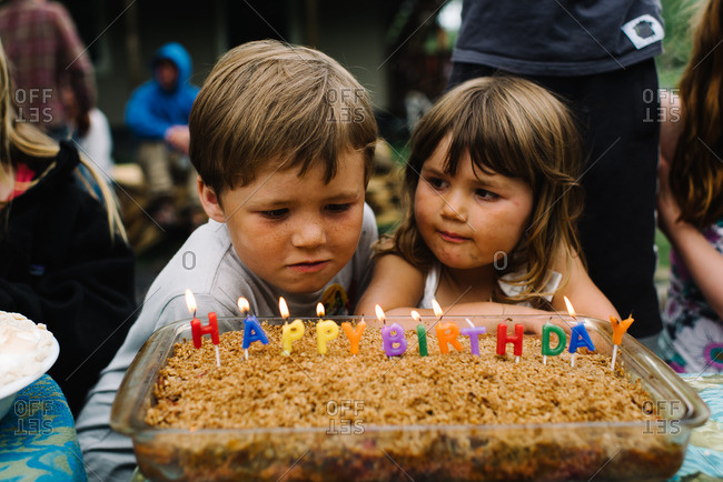 Children at a party looking at a cake that has happy birthday spelled out in candles