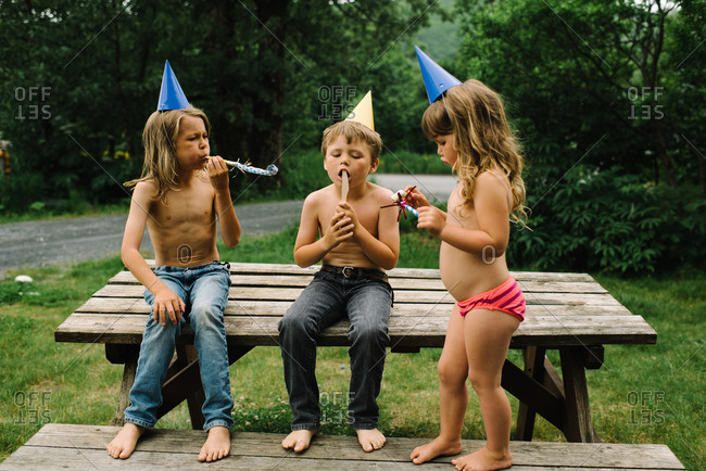 Brother and sister on a picnic table wearing party hats