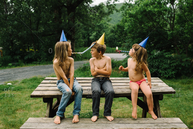 Boy sitting on a picnic table while brother and sister blow party noisemakers