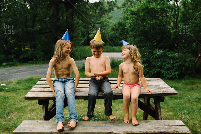 Brother and sister laughing while sitting on a picnic table at a birthday party