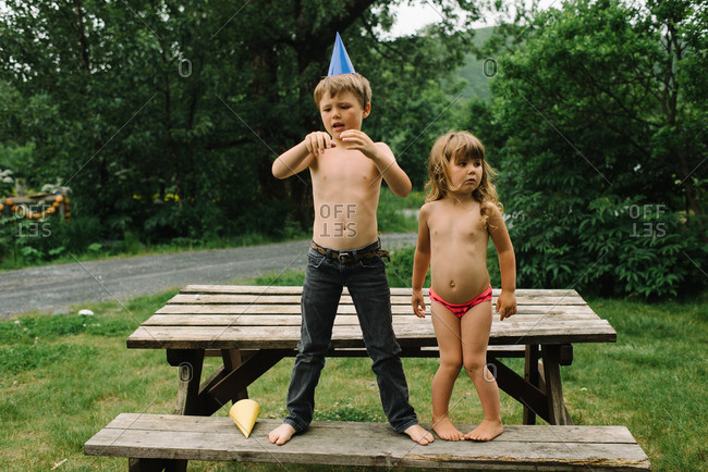 Boy wearing a party hat and his sister standing on a picnic table
