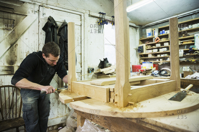 A man in a carpentry workshop, working on the edge of a new wooden table using a hammer
