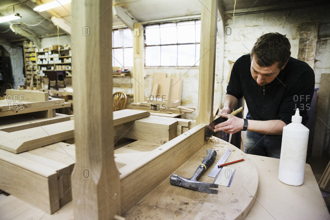Man standing in a carpentry workshop, working on the skirting of a wooden table with a hand tool
