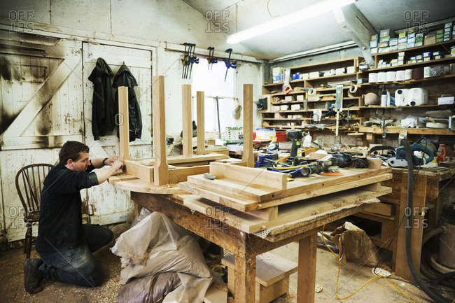 Man standing in a carpentry workshop, working on the skirting of a wooden table