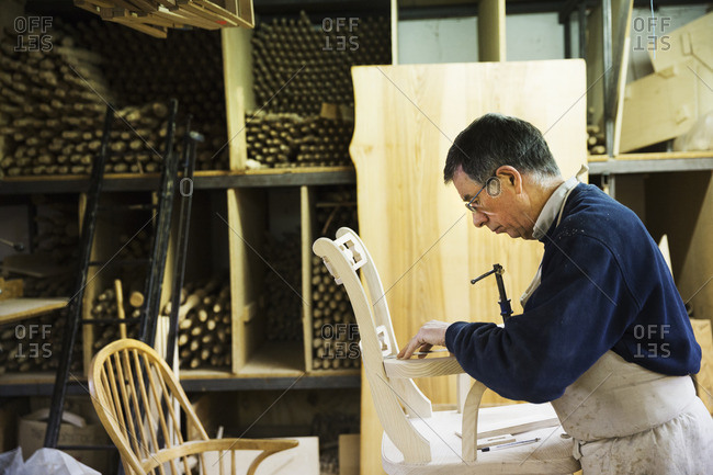 Man standing in a carpentry workshop, working on a wooden chair marking the armrest joint with a pencil