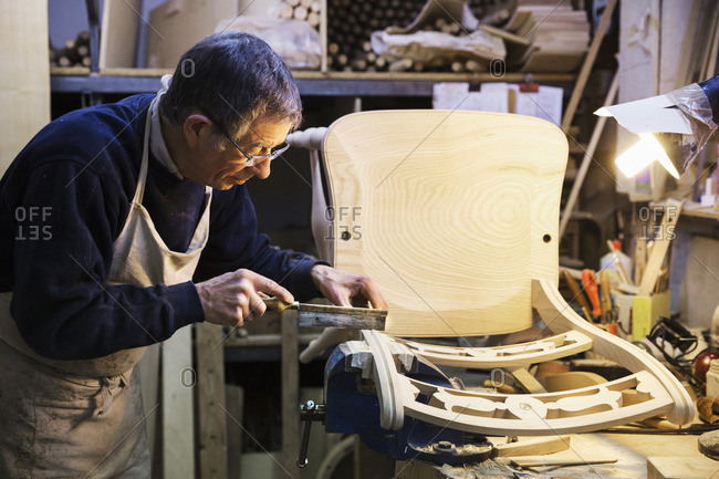 Man standing at a work bench in a carpentry workshop, working on a wooden chair with a small hand saw