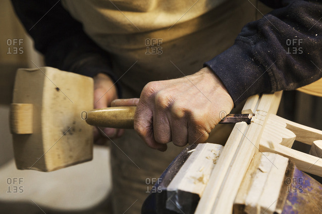 Close up of a man standing at a work bench in a carpentry workshop, working on a wooden chair with a wooden mallet and chisel