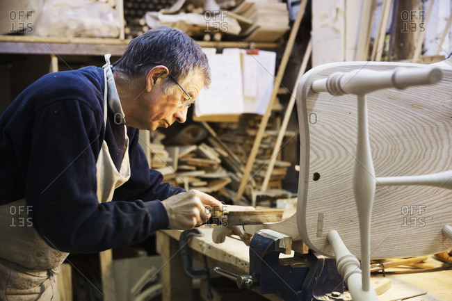 Man standing at a work bench in a carpentry workshop, working on a wooden chair