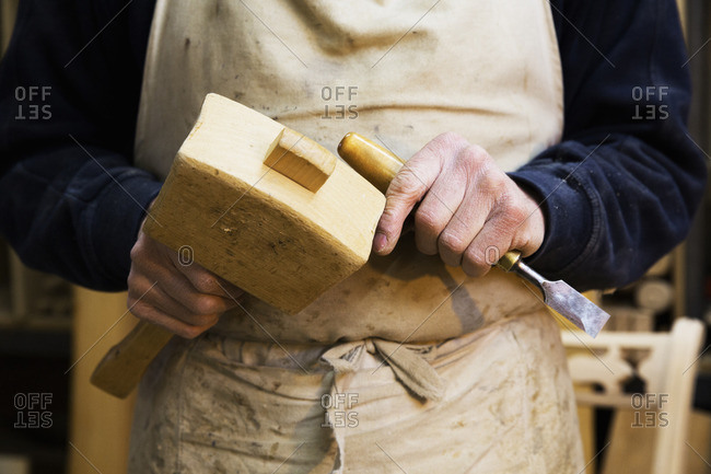 Close up of a man in a carpentry workshop, holding a wooden mallet and chisel