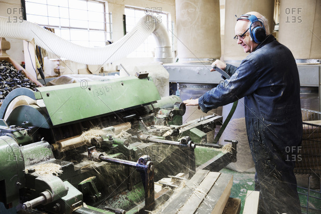 Man standing in a carpentry workshop, wearing hearing protectors, working at a woodworking machine