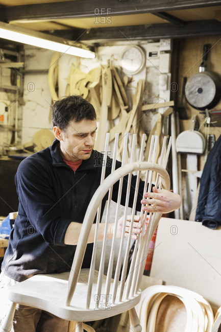 Man standing in a carpentry workshop, working on a wooden chair back