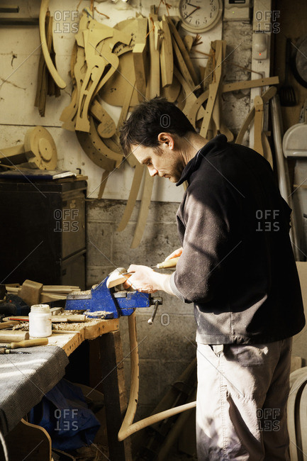 Man standing at a work bench in a carpentry workshop, working on a piece of wood secured in a bench vice