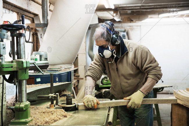 Man standing in a carpentry workshop, wearing a respirator and hearing protector, working on a piece of wood