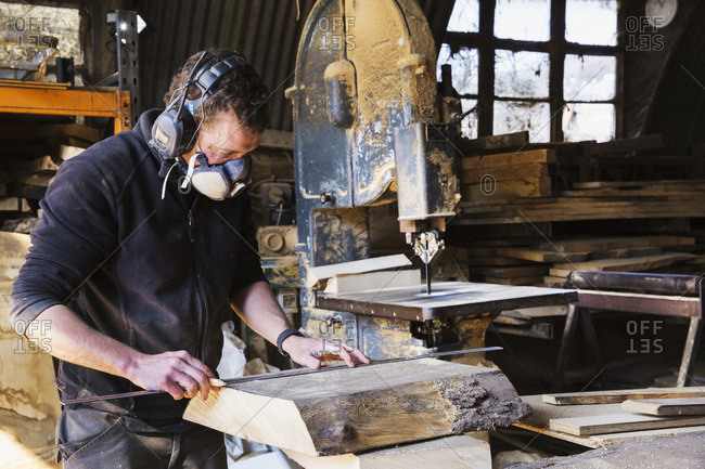 Man working in a carpentry workshop, wearing a respirator and hearing protector, measuring a plank of wood