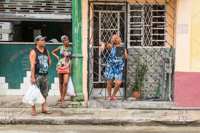 April 15, 2016: Three people on a Havana sidewalk