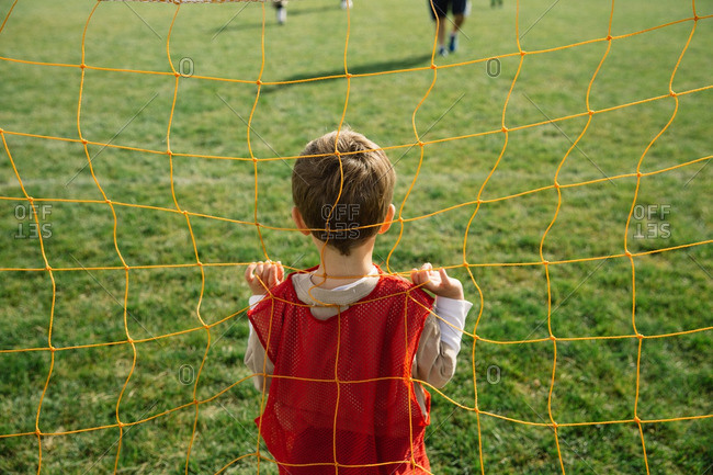 Boy standing in a soccer goal during a soccer match