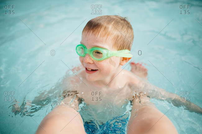 Child hanging on to his mother's legs while treading water in a swimming pool