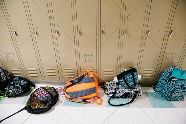 Backpacks sitting in a hallway next to a row of school lockers