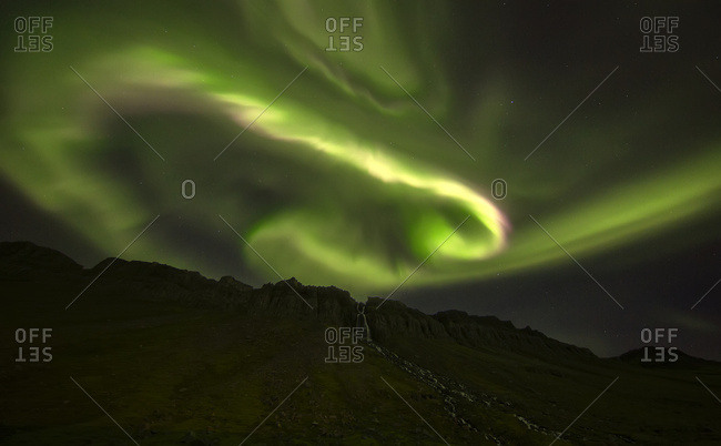 Aurora overtop of an unnamed waterfall near the town of Djupavik