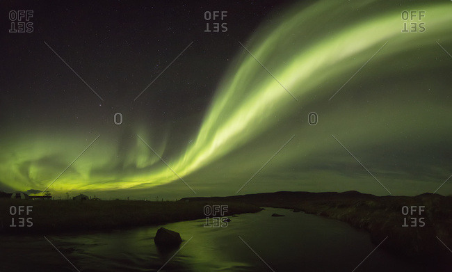 Northern lights over a river and farm in Northeast Iceland