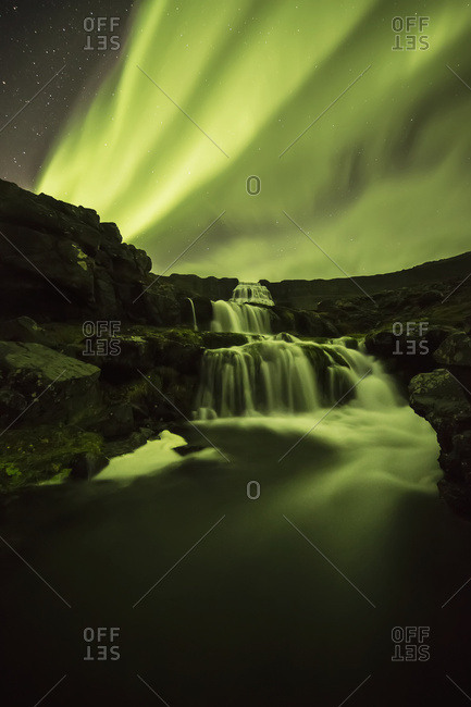 Northern Lights, or Aurora Borealis, glowing over waterfalls and a stream
