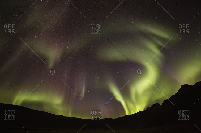 Northern Lights, or Aurora Borealis, glowing red and green over the silhouetted landscape