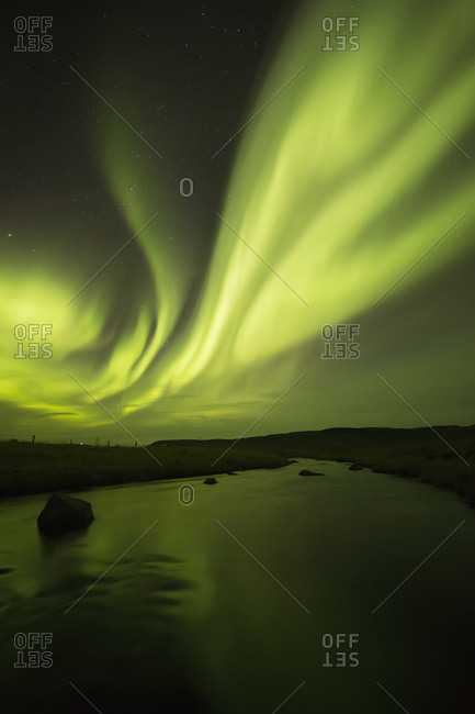 Northern Lights, or Aurora Borealis, glowing over a stream