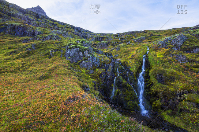 A small waterfall tumbles down the mountain side in one of Iceland eastern fjords