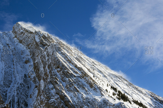 Close up of a snow covered mountain peak with wind blowing snow off the slope with blue sky and clouds