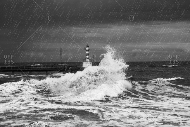 Rainfall and splashing waves with a lighthouse along the coast