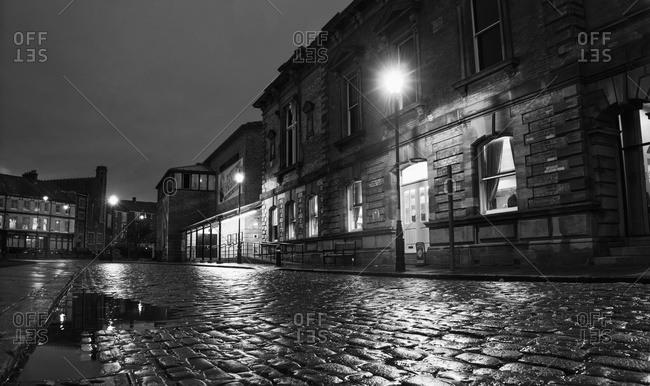 South Shields, United Kingdom - November 6, 2015: Light from a lamp post illuminating wet cobblestone road