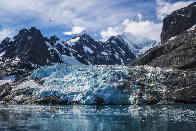 Blue glacier between snow-capped mountains and fjord
