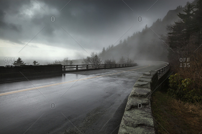 Rain on a wet bridge of North Carolina's Linn Cove Viaduct on the Blue Ridge Parkway with moody, low-hanging storm clouds and mist