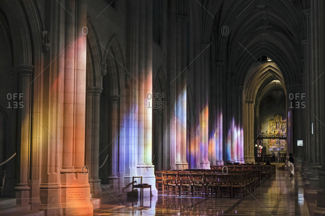 Washington DC, USA - October 16, 2015: Light streaming through stained glass windows with light columns along the cathedral nave
