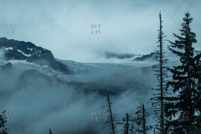 An unnamed glacier flows out of the mountains and into the clouds outside of Haines near the Alaska-Canada border