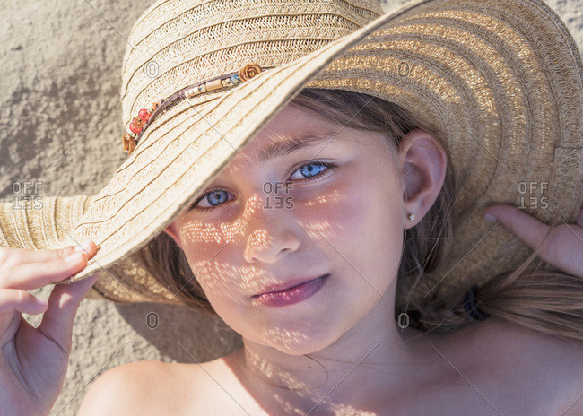A girl laying on the sand wearing a sunhat