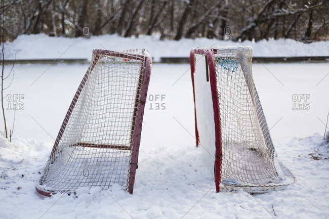 Two hockey nets in the snow beside a frozen outdoor rink