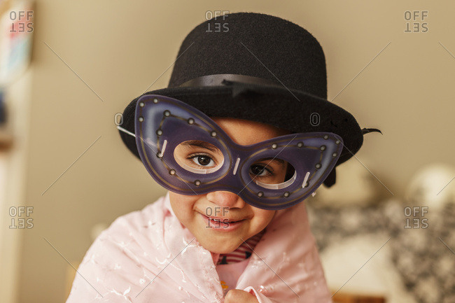 Young girl playing dress up wearing a mask and hat