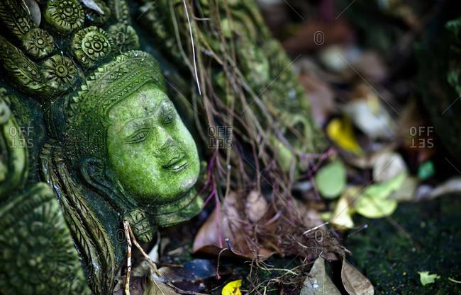 Terra-cotta sculpture of a Thai god or perhaps a temple attendant lies in ruin