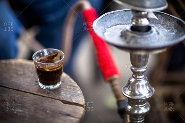 A glass of Turkish coffee sits by a sheesha