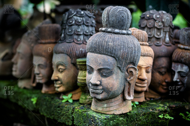 Heads of statues of Buddha are stacked in a terra-cotta factory