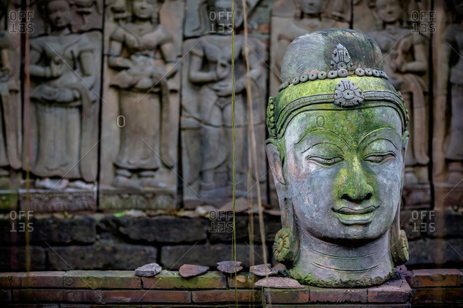 A terra cotta head of Buddha sits in front of bas-relief in a terra cotta garden