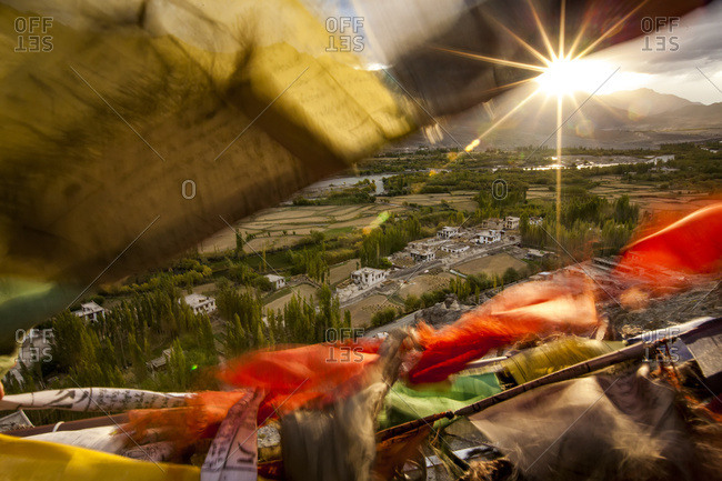 The sun sets over a Ladakhi village outside of Leh, viewed through the flapping prayer flags
