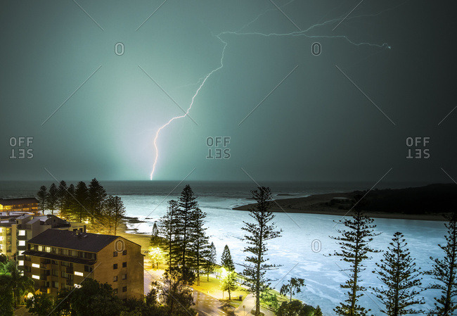 A lightning strike hits the surface of the water in the distance