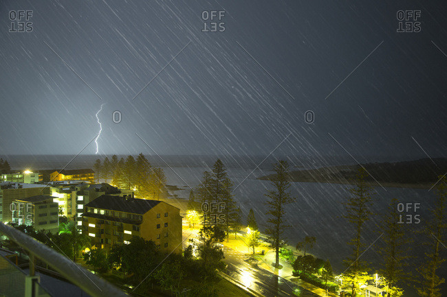 A lightning strike hits the ground in the distance and streaks of rain falling