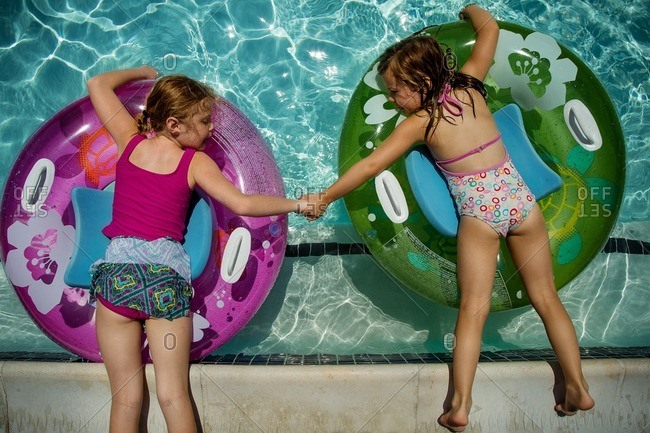 Two young girls holding hands while floating in pool