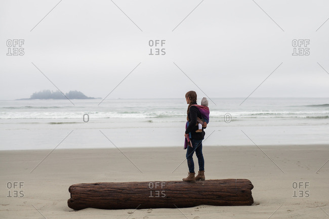 Mother with baby on back standing on log