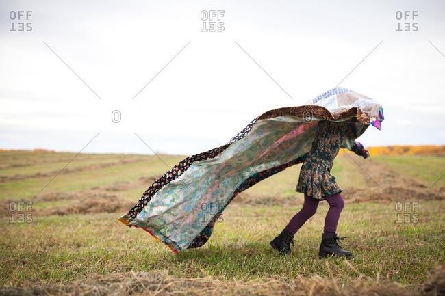 Girl holding blanket over head in field