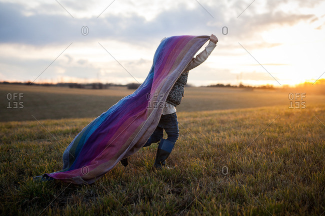 Girl running with blanket at sunset